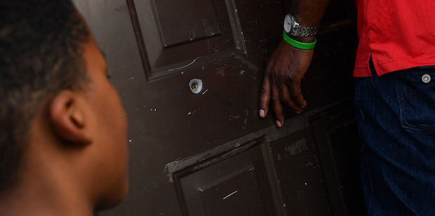 Tyshaun passes a bullet hole in the front door of his home in Southeast. Photo / Washington Post