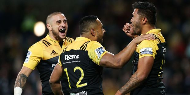 Vince Aso of the Hurricanes celebrates his try with teammates TJ Perenara and Ngani Laumape. Photo / Getty