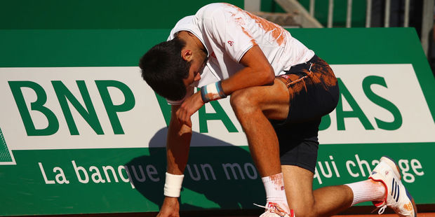 Novak Djokovic covered in clay after a tumble. Photo / Getty