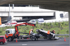 A McLaren supercar is loaded on to a recovery truck after an accident on the Great North Rd on-ramp on to the Northwestern Motorway in Auckland. Photo / Peter Meecham