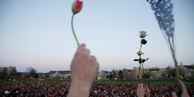 This April 17, 2007 file photo of people gathered for a vigil on the drill field following the shootings on the Virginia Tech campus in Blacksburg. Photo / AP