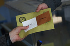 A ballot is handed to a voter inside a polling station in Ankara, Turkey. Photo / AP
