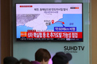 Seoul commuters watching footage of a North Korean ballistic missile. Photo / AP