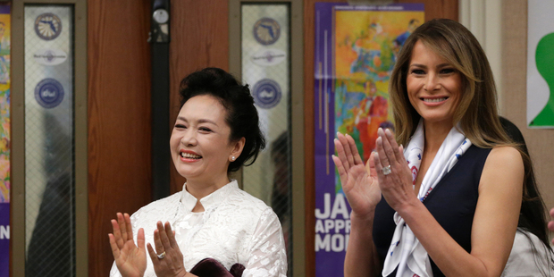 First lady Melania Trump, right, and Peng Liyuan, wife of Chinese president Xi Jinping, left, applaud while listening to an orchestra perform while touring the Bak Middle School. Photo / AP