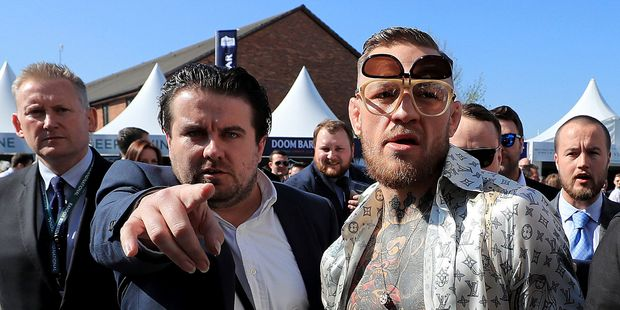 Irish boxer Conor McGregor, right, arrives on Grand National Day of the Grand National Festival at Aintree Racecourse in Liverpool. (Peter Byrne/PA via AP)