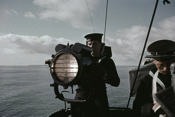 A signaller operates an Aldis lamp on board a British warship, 1942. Photo / Imperial War Museum