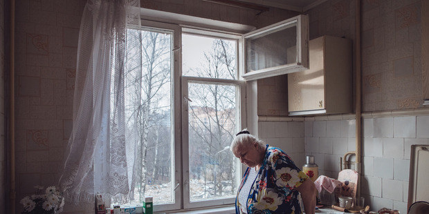 "Tatyana Chaynikova, 68, stands in her apartment in a ""khrushchevka"" building in the Belyayevo district of Moscow."