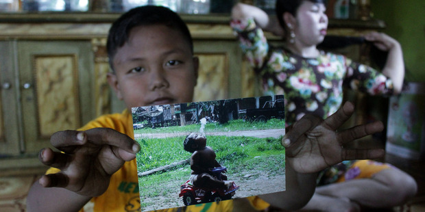 Ardi Rizal shows his photographs of smoking at the age of 2. Photo / Getty Images