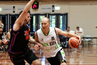 Tall Blacks legend Phill Jones drives on old rival Sam Mackinnon during their Anzac basketball clash at the World Masters Games 2017. Photo / Sylvia Wilkins