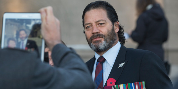 Loading Willie Apiata, VC, posing for photographs after the Anzac Day Dawn Service at the national War Memorial in Wellington. Photo / Mark Mitchell