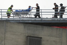 Hospital staff, ambulance and Otago Regional Rescue Helicopter crew transport a shark attack victim from the rooftop heli-pad into the Dunedin Public Hospital. Photo / Gregor Rich