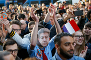A supporter wears a face mask of hard Left French presidential election candidate Jean-Luc Melenchon outside his election headquarters. Photo / AP