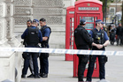 Police officers talk to a man at the scene after a person was arrested in London on Thursday. Photo / AP
