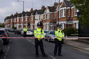 Police officers man the cordoned off area in London's Harlesden Road, after British counter-terror police have shot a woman and arrested several people in raids in London. Photo / AP
