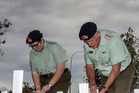 Lance Corporal Hannah Scott-Bennie and Ruahine Cadet Unit Captain Ross Unwin place the crosses at the Anzac sunset service in Waipukurau last night. Photo/ Paul Taylor.