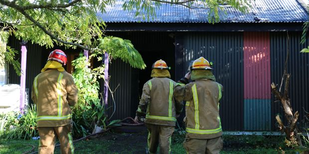 Firefighters continue to dampen hotspots at the Olivers' family home in Mauriceville. Photo /Hayley Gastmeir
