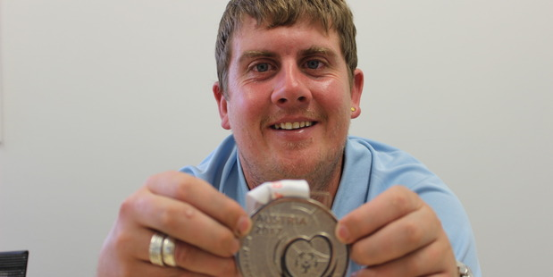 Jason Donovan with his silver medal from the Special Olympics World Winter Games.