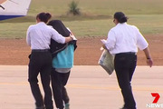 Tayla Perkin, 18, boards a plane under police guard after being charged with murdering her grandfather. Photo / 7News