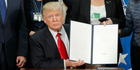 President Trump holds up an executive order to start the Mexico border wall project on January 25. Photo / AP