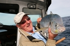 The writer with a large trevally taken at White Island on a fly rod. Photo / Geoff Thomas
