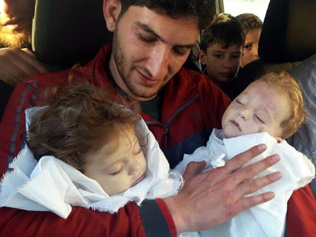 Abdul-Hamid Alyousef holds his twin babies who were killed by a chemical weapons attack in Khan Sheikhoun. Photo/AP