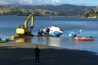 The helicopter is salvaged from the water near Porirua. Photo / Melissa Nightingale
