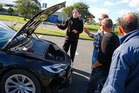 Carl Barlev shows the inner workings of his Tesla electric car to interested car enthusiasts. Photo/Bevan Conley