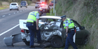 Police inspect the car involved in the crash. Photo/Stephen Parker