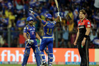 Mumbai Indians' player Rohit Sharma, left, and Krunal Pandya, center, celebrate their win as Shane Watson, right, of Royal Challengers Bangalore stands beside them. Photo / AP.
