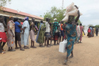 A South Sudanese woman carries food donated by Saudi Arabia Government through the Islamic Council of South Sudan. Photo / AP