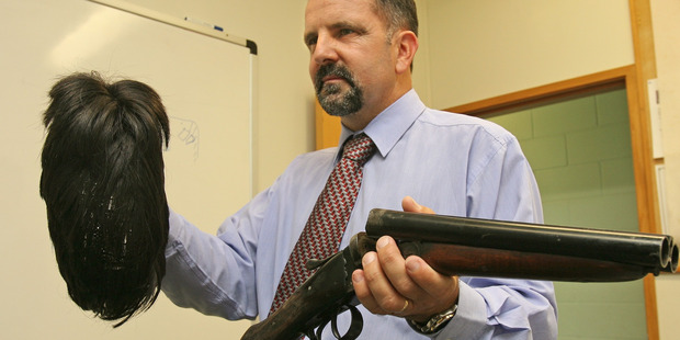 Detective Sergeant David French holding the wig and sawn off shotgun used in the Tissot robbery. Photo/NZ Herald.