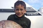 Awarua WiHongi, 7, with the massive 9kg snapper he caught on a fishing trip over Easter weekend. photo/ supplied