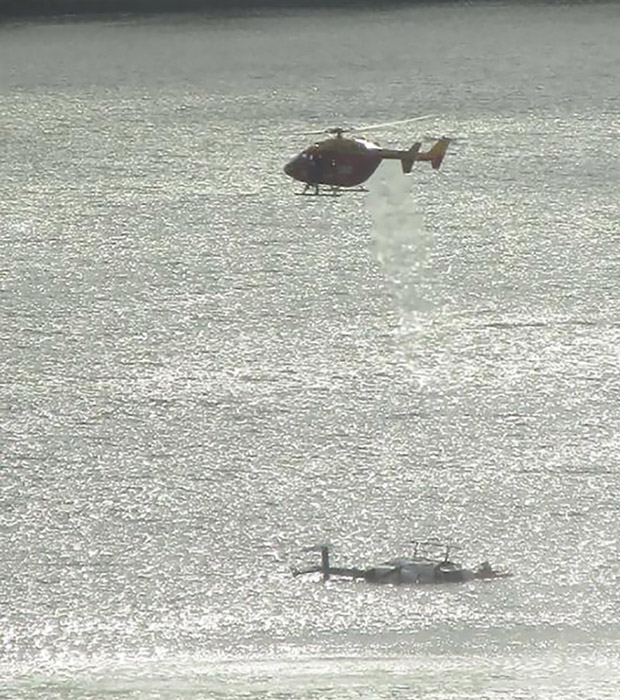 A rescue helicopter hovers above the a helicotper that ditched in the lagoon at Porirua, orth of Wellington, Tuesday. Picture / Georgina Russell