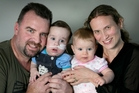 Craig and Selina Johnson at home yesterday with their 9-month-old twins, Jacob (left) and Emma. Photo / Supplied