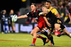 Israel Dagg of the Crusaders passes the ball in the tackle of TJ Perenara of the Hurricanes during the Super Rugby Match. Photo / Photosport