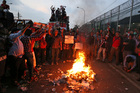 Supporters of Jakarta Governor Basuki 'Ahok' Tjahaja Purnama shout slogans as they burn tires during a rally outside Cipinang Prison where he is being held. Photo / AP