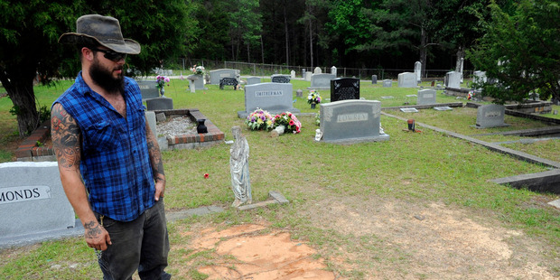 Tyler Goodson of the hit podcast S-Town stands at the grave of friend John B McLemore, who is also featured in the serialized show. Photo/AP