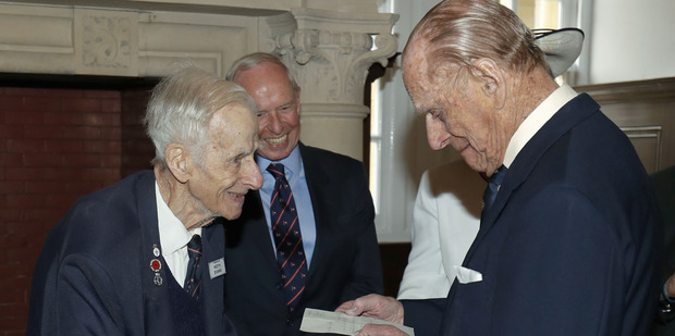 Loading Prince Philip, Duke of Edinburgh reads a letter he wrote to former naval commander Keith Evans, left, now aged 97, after the announcement of his engagement to Queen Elizabeth. Photo / Getty
