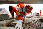 A firefighter searches for the trapped people during an earthquake exercise on May 9, 2017 in Meishan, Sichuan Province of China. Photo / Getty Images