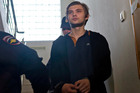 Handcuffed blogger Ruslan Sokolovsky is escorted by police officers in a court building in Yekaterinburg, Russia last year. Photo / AP