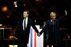 French President-elect Emmanuel Macron holds hands with his wife Brigitte during a victory celebration. Photo / AP