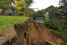 John Cufflin, who lives in Kowai Grove, Omokoroa standing at the edge of major slip which took out part of his backyard and a major chunk of the neighbouring property. Photo/File