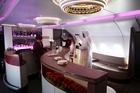 Flight crew show visitors through the bar area for business class passengers aboard an Airbus A380-800 aircraft, operated by Qatar Airways Ltd. Photo / Bloomberg