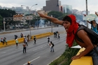 Anti-government protesters direct their colleagues during running battles with members of the national guard in Caracas. Photo / AP