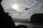 Firefighters and helicopters with monsoon buckets battle scrub fires in Piha this morning