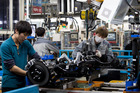 Employees assemble vehicle chassis on a production line at Hyundai factory in South Korea. Photo / SeongJoon Cho