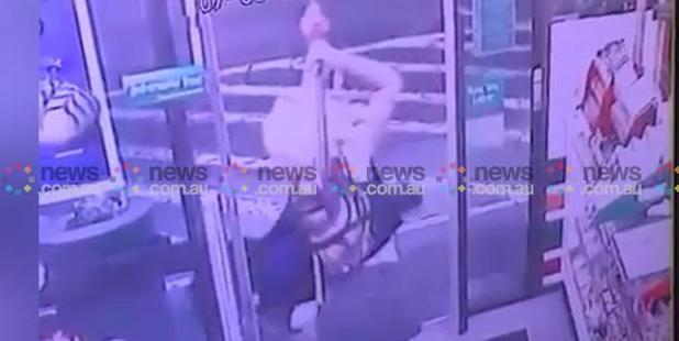 Loading A stunned Mr Rimmer lies reeling on the ground as the woman takes a second swing of the axe at the prostrate Sharon Hacker who has collapsed outside the shop door. Photo / News.com.au