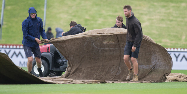 Ground staff hauling the covers over the pitch after rain stopped play on day one of the cricket test at the Basin Reserve. Photo / Mark Mitchell