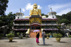 Visitors view the Golden Buddha statue at the Golden Temple of Dambulla in Sri Lanka. Photo / Bloomberg