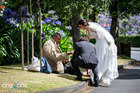 Bronia Tindall and Fabrizio Clementi share a slice of their wedding cake with a homeless man outside The Community of St Luke church in Remuera. Photo / Ben Franks/Steve May/one2one Photography